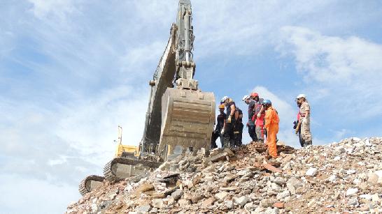 Pala Excavadora, inicia excavación para posterior sepultamiento completo de persona protegida por una estructura hermetizable ( XXXVI Curso Internacional Método Arcón )